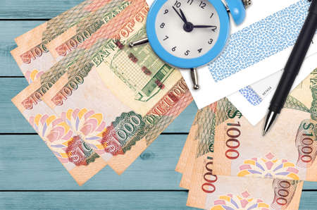 1000 Guyanese dollars bills and alarm clock with pen and envelopes. Tax season concept, payment deadline for credit or loan. Financial operations using postal service. Quick money transfer