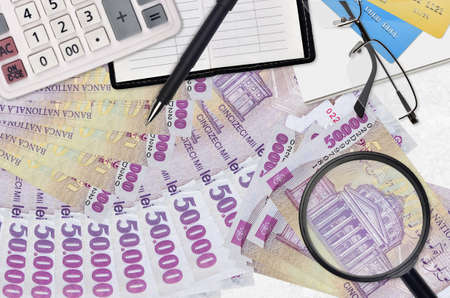50,000 Romanian leu bills and calculator with glasses and pen. Tax payment season concept or investment solutions. Searching a job with high salary earnings