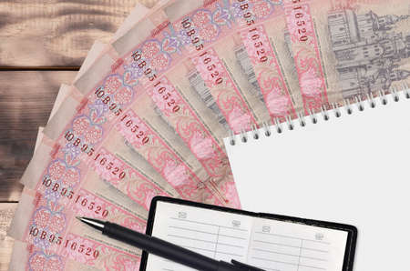10 Ukrainian hryvnias bills fan and notepad with contact book and black pen. Concept of financial planning and business strategy. Accounting and investment Stock Photo