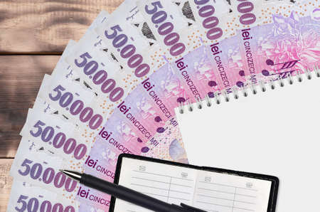 50,000 Romanian leu bills fan and notepad with contact book and black pen. Concept of financial planning and business strategy. Accounting and investment