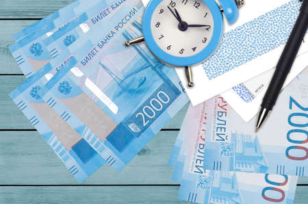 2000 russian rubles bills and alarm clock with pen and envelopes. Tax season concept, payment deadline for credit or loan. Financial operations using postal service. Quick money transfer