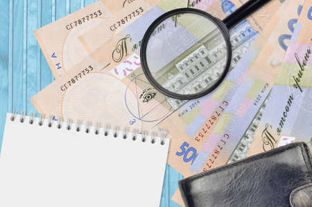 500 Ukrainian hryvnias bills and magnifying glass with black purse and notepad. Concept of counterfeit money. Search for differences in details on money bills to detect fake money