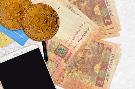 2 Ukrainian hryvnias bills and golden bitcoins with smartphone and credit cards. Cryptocurrency investment concept. Crypto mining or trading transactions