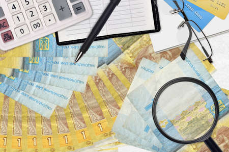 1 Ukrainian hryvnia bills and calculator with glasses and pen. Tax payment season concept or investment solutions. Searching a job with high salary earnings