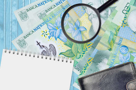 1 Romanian leu bills and magnifying glass with black purse and notepad. Concept of counterfeit money. Search for differences in details on money bills to detect fake money