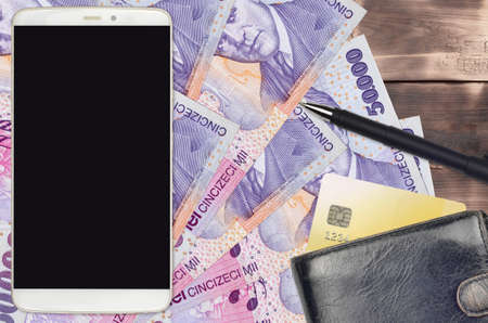 50,000 Romanian leu bills and smartphone with purse and credit card. E-payments or e-commerce concept. Online shopping and business with portable devices usage