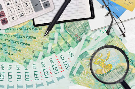 1 Romanian leu bills and calculator with glasses and pen. Tax payment season concept or investment solutions. Searching a job with high salary earnings