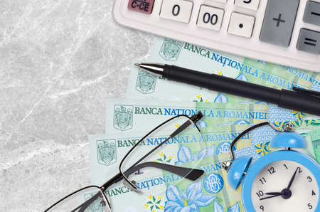 1 Romanian leu bills and calculator with glasses and pen. Business loan or tax payment season concept. Financial planning and time to pay taxes
