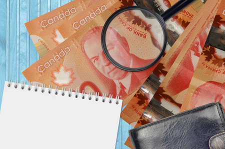 50 Canadian dollars bills and magnifying glass with black purse and notepad. Concept of counterfeit money. Search for differences in details on money bills to detect fake money