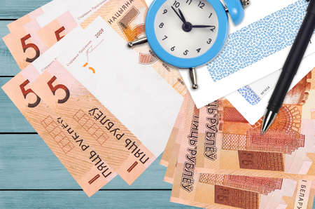 5 Belorussian rubles bills and alarm clock with pen and envelopes. Tax season concept, payment deadline for credit or loan. Financial operations using postal service. Quick money transfer