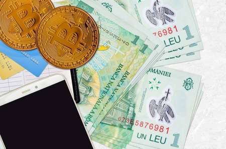 1 Romanian leu bills and golden bitcoins with smartphone and credit cards. Cryptocurrency investment concept. Crypto mining or trading transactions