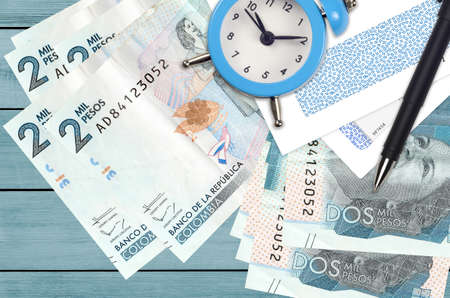 2 Colombian pesos bills and alarm clock with pen and envelopes. Tax season concept, payment deadline for credit or loan. Financial operations using postal service. Quick money transfer Фото со стока