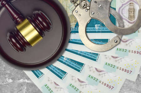 5 British pounds bills and judge hammer with police handcuffs on court desk. Concept of judicial trial or bribery. Tax avoidance or tax evasion