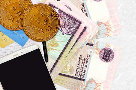 20 Sri Lankan rupees bills and golden bitcoins with smartphone and credit cards. Cryptocurrency investment concept. Crypto mining or trading transactions