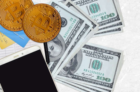 100 US dollars bills and golden bitcoins with smartphone and credit cards. Cryptocurrency investment concept. Crypto mining or trading transactions