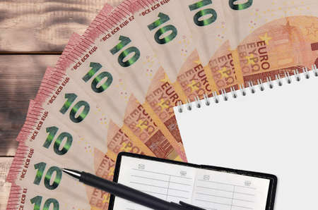 10 euro bills fan and notepad with contact book and black pen. Concept of financial planning and business strategy. Accounting and investment Stock Photo