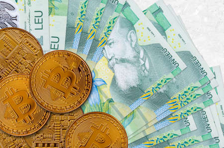 1 Romanian leu bills and golden bitcoins. Cryptocurrency investment concept. Crypto mining or trading transactions