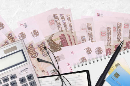 100 russian rubles bills and calculator with glasses and pen. Tax payment season concept or investment solutions. Financial planning or accountant paperwork