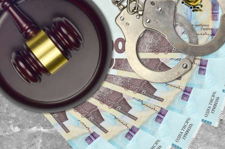 1000 Ukrainian hryvnias bills and judge hammer with police handcuffs on court desk. Concept of judicial trial or bribery. Tax avoidance or tax evasion Stock Photo