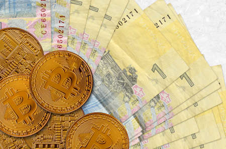 1 Ukrainian hryvnia bills and golden bitcoins. Cryptocurrency investment concept. Crypto mining or trading transactions