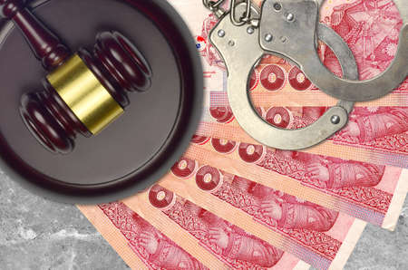 100 Thai Baht bills and judge hammer with police handcuffs on court desk. Concept of judicial trial or bribery. Tax avoidance or tax evasion Stock Photo