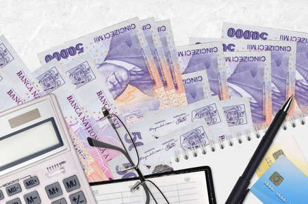 50,000 Romanian leu bills and calculator with glasses and pen. Tax payment season concept or investment solutions. Financial planning or accountant paperwork