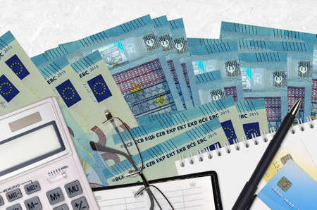20 euro bills and calculator with glasses and pen. Tax payment season concept or investment solutions. Financial planning or accountant paperwork