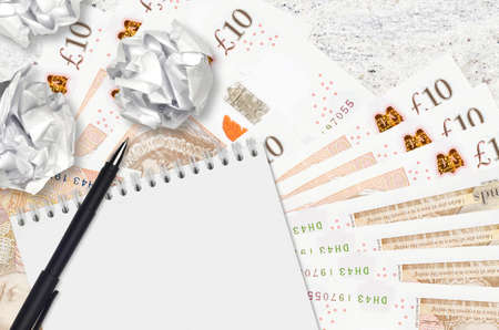 10 British pounds bills and balls of crumpled paper with notepad. Bad ideas or less of inspiration concept. Searching ideas for investment