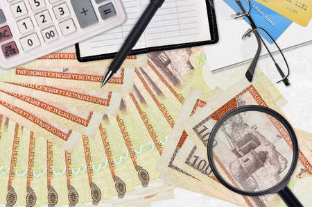 100 Dominican peso bills and calculator with glasses and pen. Tax payment season concept or investment solutions. Searching a job with high salary earnings
