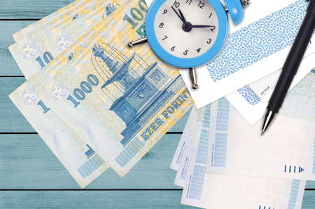 1000 Hungarian forint bills and alarm clock with pen and envelopes. Tax season concept, payment deadline for credit or loan. Financial operations using postal service. Quick money transfer