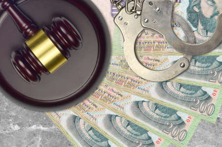 200 Hungarian forint bills and judge hammer with police handcuffs on court desk. Concept of judicial trial or bribery. Tax avoidance or tax evasion