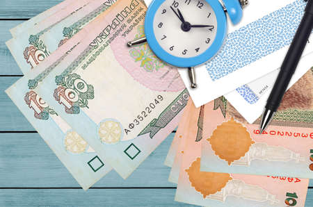 100 Ukrainian hryvnias bills and alarm clock with pen and envelopes. Tax season concept, payment deadline for credit or loan. Financial operations using postal service. Quick money transfer