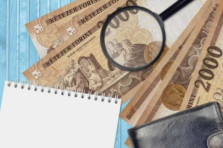 2000 Hungarian forint bills and magnifying glass with black purse and notepad. Concept of counterfeit money. Search for differences in details on money bills to detect fake money