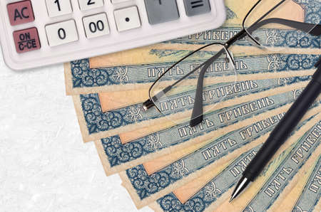 5 Ukrainian hryvnias bills fan and calculator with glasses and pen. Business loan or tax payment season concept. Financial planning Standard-Bild