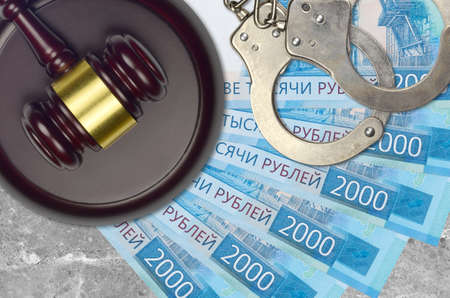 2000 russian rubles bills and judge hammer with police handcuffs on court desk. Concept of judicial trial or bribery. Tax avoidance or tax evasion
