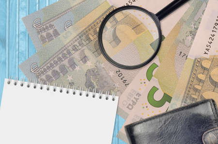 5 euro bills and magnifying glass with black purse and notepad. Concept of counterfeit money. Search for differences in details on money bills to detect fake money