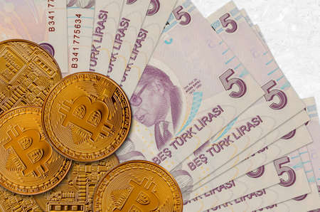 5 Turkish lira bills and golden bitcoins. Cryptocurrency investment concept. Crypto mining or trading transactions