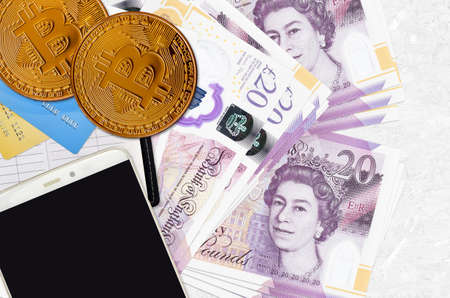 20 British pounds bills and golden bitcoins with smartphone and credit cards. Cryptocurrency investment concept. Crypto mining or trading transactions Imagens