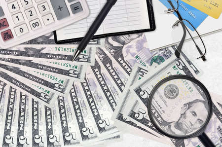 5 US dollars bills and calculator with glasses and pen. Tax payment season concept or investment solutions. Searching a job with high salary earnings
