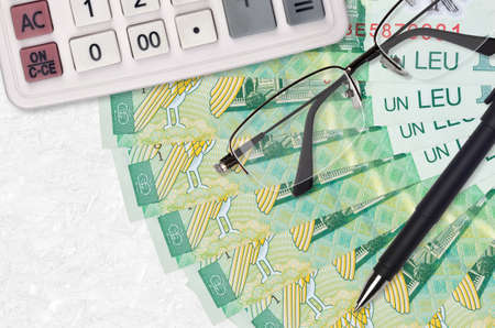 1 Romanian leu bills fan and calculator with glasses and pen. Business loan or tax payment season concept. Financial planning