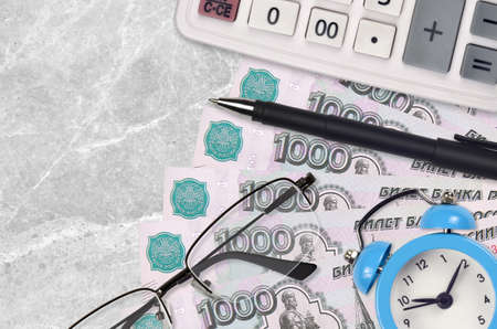 1000 russian rubles bills and calculator with glasses and pen. Business loan or tax payment season concept. Financial planning and time to pay taxes Фото со стока