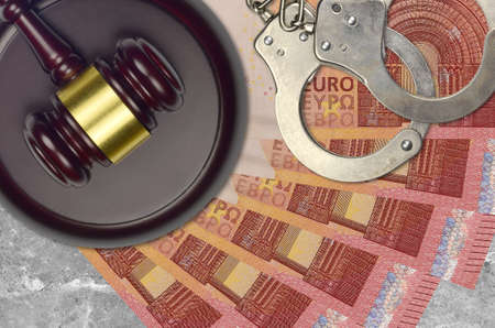 10 euro bills and judge hammer with police handcuffs on court desk. Concept of judicial trial or bribery. Tax avoidance or tax evasion