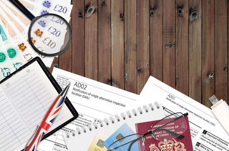 English form AD02 Notification of single alternative inspection location SAIL from Companies House service lies on table with office items. CH business and paperwork process in United Kingdom