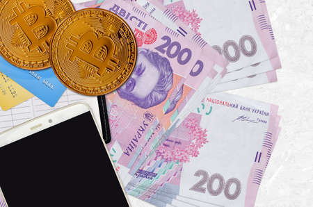 200 Ukrainian hryvnias bills and golden bitcoins with smartphone and credit cards. Cryptocurrency investment concept. Crypto mining or trading transactions