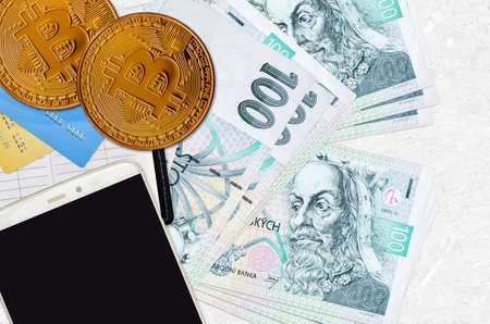 100 Czech korun bills and golden bitcoins with smartphone and credit cards. Cryptocurrency investment concept. Crypto mining or trading transactions