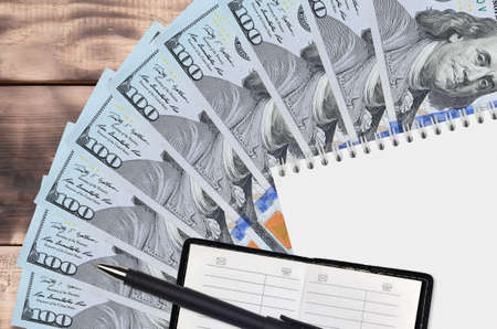 100 US dollars bills fan and notepad with contact book and black pen. Concept of financial planning and business strategy. Accounting and investment Stock Photo