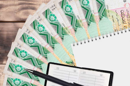 10 Sri Lankan rupees bills fan and notepad with contact book and black pen. Concept of financial planning and business strategy. Accounting and investment