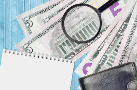 5 US dollars bills and magnifying glass with black purse and notepad. Concept of counterfeit money. Search for differences in details on money bills to detect fake money