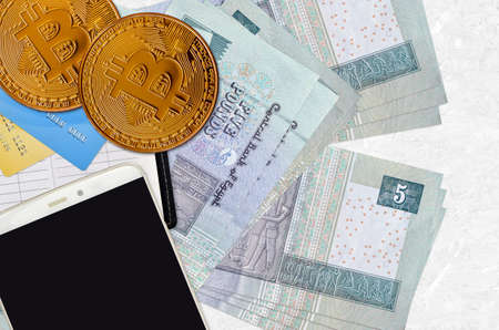 5 Egyptian pounds bills and golden bitcoins with smartphone and credit cards. Cryptocurrency investment concept. Crypto mining or trading transactions
