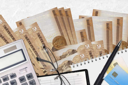 2000 Hungarian forint bills and calculator with glasses and pen. Tax payment season concept or investment solutions. Financial planning or accountant paperwork